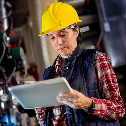 Woman wearing a hard hat with an iPad.