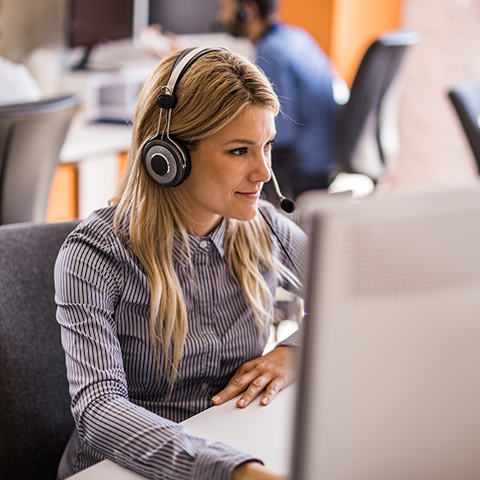 Woman working in the back office with headset.