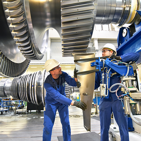 Two individuals in uniform wearing hard hats working on a large machine.